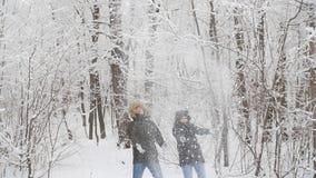 Gå för vinter och turismbegrepp Unga lyckliga par går och har gyckel i skogen i vinter stock video