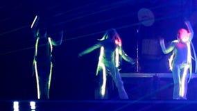 G?-g?r flickor dansar i neondr?kter av kaniner arkivfilmer