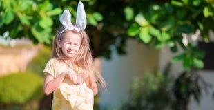 Gå i ax den bärande kaninen för den förtjusande lilla flickan med påskägg på vårdag royaltyfri bild