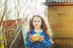 Gå i ax den bärande kaninen för den gulliga flickan rymma en korg med påskägg Royaltyfri Foto