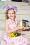 Gå i ax den roliga flickan för lilla barnet med kaninen hemma klart att fira sp Arkivfoton