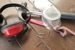 Gå i ax muffs, ögonskydd, hammare, spikar, blyertspennan på timmerbakgrund Fotografering för Bildbyråer