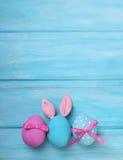 Gå i ax rosa och blåa ägg för påsk med kaninen royaltyfria bilder