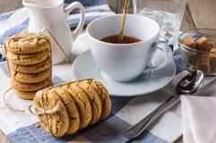 Gå i flisor kakor, en kopp te, socker, mjölka, exponeringsglas av isvatten Royaltyfri Bild