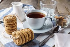 Gå i flisor kakor, en kopp te, socker, mjölka, exponeringsglas av isvatten Arkivfoton