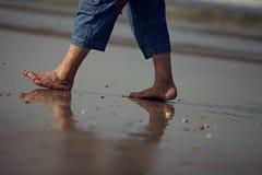 Gå i sanden med smutsig fot Arkivfoton