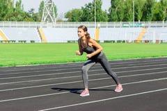 gå klar till Nära övre foto av den kvinnliga idrottsman nen på startande linje för hög start Flicka på stadionspåret som förbered royaltyfria bilder