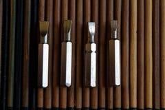 Gå mot skruvmejselbitar på träbakgrund, hjälpmedelsamlingsvänd-skruv Arkivfoton