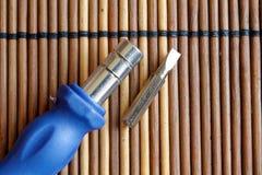 Gå mot skruvmejselbiten med vänd-skruven på träbakgrund, hjälpmedelsamling Royaltyfria Foton