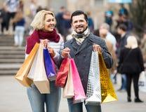 Gå och bärande shoppingpåsar för åldringpar Arkivbild