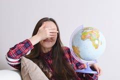 Gå på ett affärsföretag Den roliga kvinnan som drömmer om att resa runt om världen, vridet ett jordklot och, stänger ögon Lycklig Arkivfoto