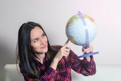 Gå på ett affärsföretag Kvinna som drömmer om att resa runt om världen och att se jordklotet i rum av huset Nätt flickastudie Royaltyfri Foto