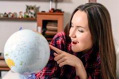 Gå på ett affärsföretag Kvinna som drömmer om att resa runt om världen och att se jordklotet i rum av huset Nätt flickastudie Arkivbild