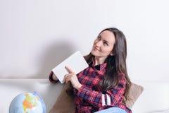 Gå på ett affärsföretag Nätt kvinna som drömmer om att resa runt om världen och att göra anmärkningar i en dagbok med länder för  Royaltyfri Bild
