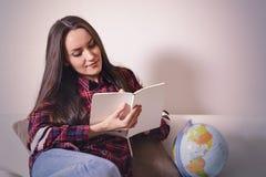 Gå på ett affärsföretag Nätt kvinna som drömmer om att resa runt om världen och att göra anmärkningar i en dagbok med länder för  Royaltyfri Foto