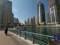 Gå promenad på den Dubai marina med sikt av byggnader och yachten i marina royaltyfri fotografi