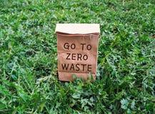 Gå till noll förlorade ekologiska shoppa påse på det gröna gräset royaltyfri foto