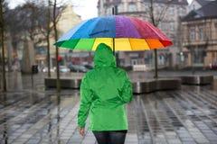 Gå till och med regnet med ett paraply och en regnrock arkivfoton