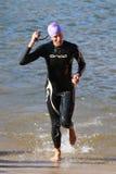gå ut från vatten för racebadtriathlonen Arkivfoton