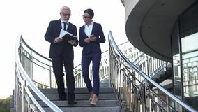 Gående bottenvåning för gammal aktieägare med den kvinnliga sekreteraren som förbereder sig för presentation royaltyfri foto