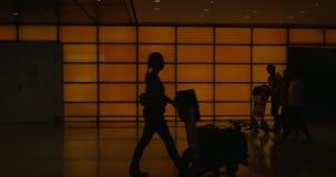 Gående folk med luggages längs korridor mot den upplysta orange väggen lager videofilmer