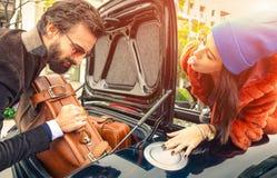 Gående semestrar för härliga modepar som laddar deras bil Arkivbild