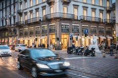 Gångare och biltrafik på en typisk shoppa gata i i stadens centrum Milan fotografering för bildbyråer