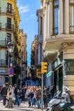 Gångare och en motorcyklist på trafikljus på gatan i Barcelona, Spanien royaltyfri bild