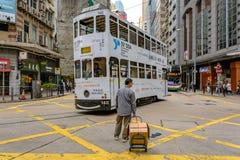 Gångare- och kabelbil på tvärgatorna i Hong Kong Street Royaltyfri Foto