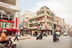 Gångare och motorcyklar som flyttar sig förbi diversehandel på den upptagna indiska gatan Arkivbilder
