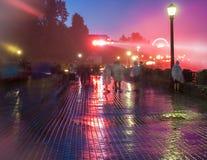 Gångare på en regnig färgrik gångbana Arkivfoto