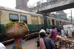 Gångare rickshaws, cyklister som väntar på järnvägkorsning i Kolkata Arkivfoton