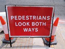 Gångare ser båda vägar, varnande tecken för gataarbeten royaltyfri bild