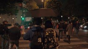 Gångare som korsar gatan på gröna trafikljus i nattstad france paris stock video