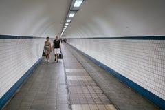 Gångare som passerar en fotvandra tunnel under floden Schelde på Antwerp, Belgien Arkivbilder