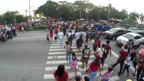 Gångare som promenerar den fot- vägen för att korsa gatan arkivfilmer