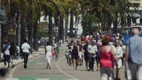 Gångare som strosar långsamt i gata, många turister och lokaler i semesterortstad arkivfilmer