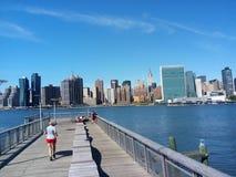 Gångare tycker om den nya strandpromenaden i Queens som ut ser på Manhattan Royaltyfri Bild