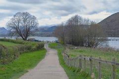 Gångbana från Pooley broby till den sceniska lakesiden av Ullswater i sjöområdesnationalparken, England, UK Arkivfoton