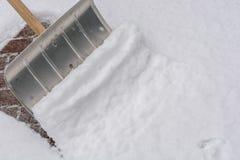 Gångbanan göras klar av snö efter ett snöfall med en snöskyffel royaltyfri foto