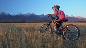 Går caucasian barn ett med cykeln i vetefält Flicka som går den svarta orange cirkuleringen på bakgrund av härligt snöig stock video