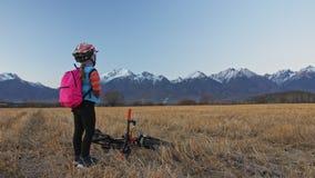 Går caucasian barn ett med cykeln i vetefält Flicka som går den svarta orange cirkuleringen på bakgrund av härligt snöig lager videofilmer