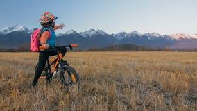 Går caucasian barn ett med cykeln i vetefält Liten flicka som går den svarta orange cirkuleringen på bakgrund av härligt royaltyfria foton