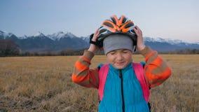 Går caucasian barn ett med cykeln i vetefält Liten flicka som går den svarta orange cirkuleringen på bakgrund av härligt royaltyfri bild