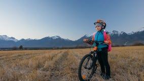 Går caucasian barn ett med cykeln i vetefält Liten flicka som går den svarta orange cirkuleringen på bakgrund av härligt fotografering för bildbyråer