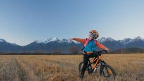 Går caucasian barn ett med cykeln i vetefält Liten flicka som går den svarta orange cirkuleringen på bakgrund av härligt royaltyfria bilder