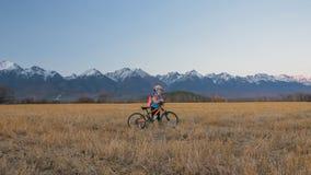 Går caucasian barn ett med cykeln i vetefält Liten flicka som går den svarta orange cirkuleringen på bakgrund av härligt arkivfoton