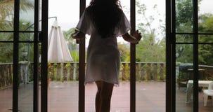 Går den öppna balkongen för flickan ut att terrassera tillbaka den bakre sikten, morgonsikt av vändkretsskogen arkivfilmer
