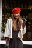 Går den iklädda stilfulla gråa klänningen för den trendiga flickan, det korta fårskinnlaget, handskar och den röda basker i parke fotografering för bildbyråer