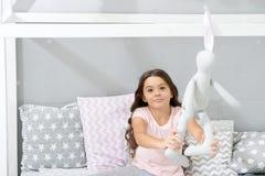 Går den mjuka leksaken för lek för sömn Tycker om långt lockigt hår för flickan aftontid med den favorit- leksaken Ungen sitter s arkivfoton